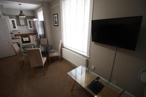 Una televisión o centro de entretenimiento en Flat 2 Broad Court