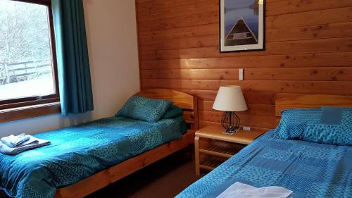 A bed or beds in a room at Loch Insh Chalets Ltd