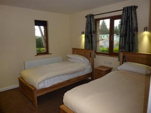 A bed or beds in a room at Elderbeck Lodge, Pooley Bridge Holiday Park