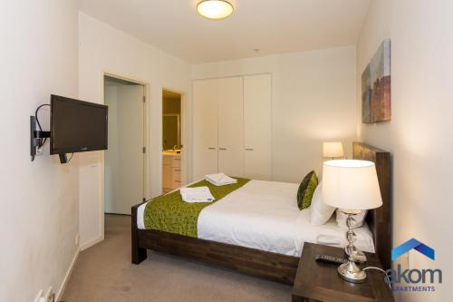 A bed or beds in a room at AKOM Docklands