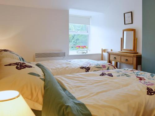 A bed or beds in a room at Capel Fawnog Mawr