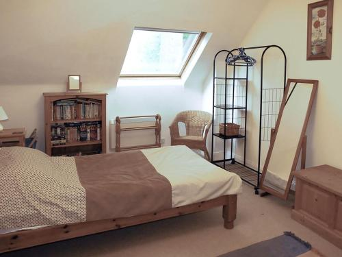 A bed or beds in a room at Old Stable Cottage