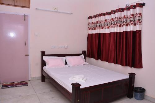 A bed or beds in a room at Aishwaryam Gowri Service Apartment Chokkikulam