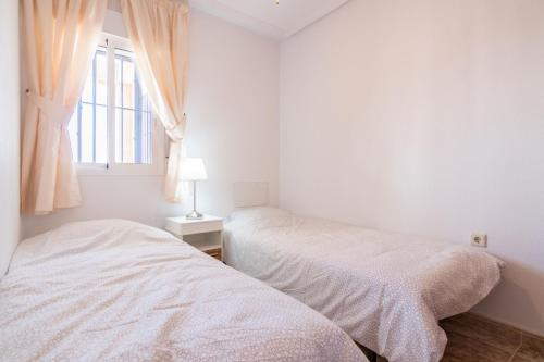 A bed or beds in a room at Apartment i Punta Prima TN