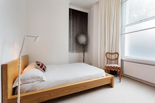 A bed or beds in a room at Beautiful Notting Hill Garden Apartment