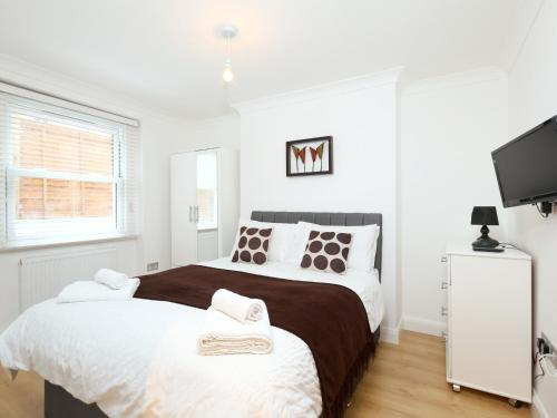 A bed or beds in a room at OYO Home Kings Cross-St Pancras Garden 4 Bedroom