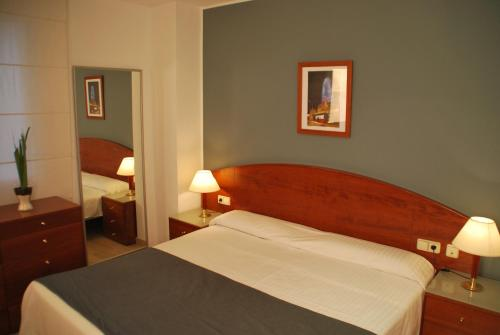 A bed or beds in a room at Aparthotel Napols - Abapart