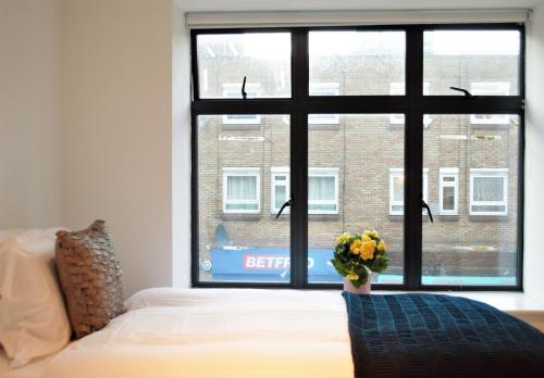 A bed or beds in a room at The Hoxton Street Apartment