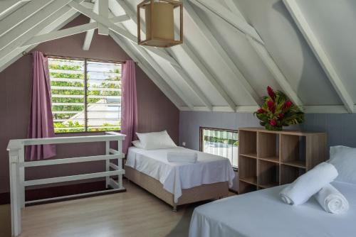A bed or beds in a room at Matira Sunset House
