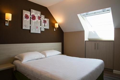 A bed or beds in a room at Appart'hotel-Park hotel