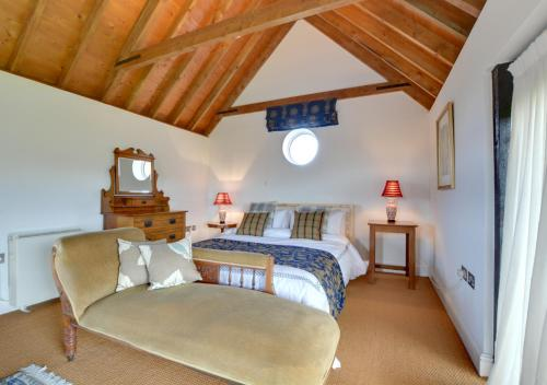 A bed or beds in a room at Oast Barn Cottage