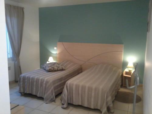A bed or beds in a room at Au Coeur Des Landes