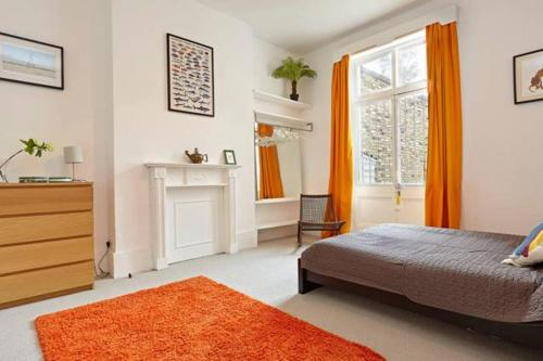 A bed or beds in a room at Perfectly located Chiswick 2 bed garden + parking