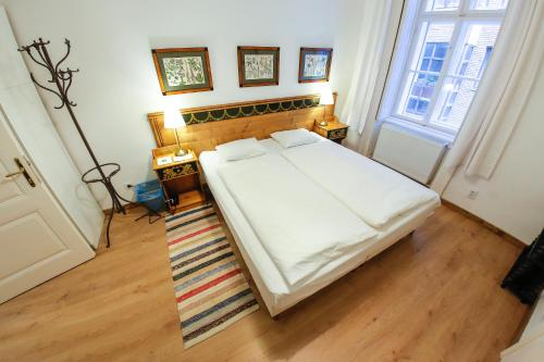 A bed or beds in a room at Holló Atelier II.
