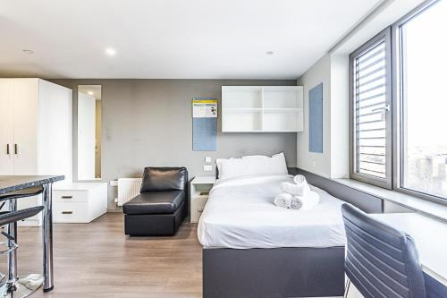 A bed or beds in a room at Studio Apartments, STRATFORD - SK.