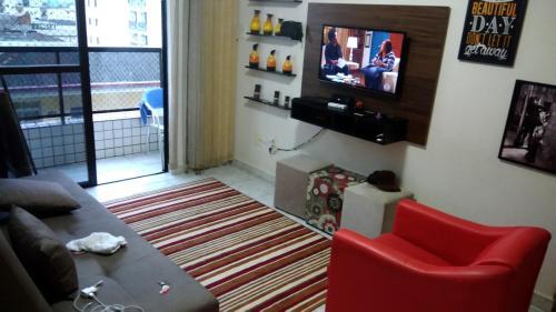 A television and/or entertainment center at Apartamento na Praia Grande