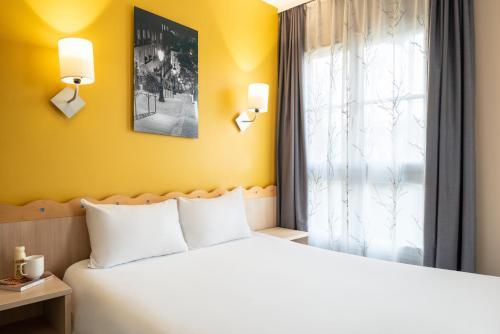 アパートホテル アダージョ マルヌ ラ ヴァレ ヴァル ドーロップにあるベッド