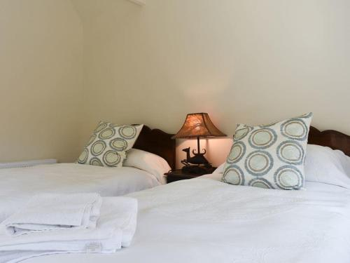 A bed or beds in a room at Potash Cottage