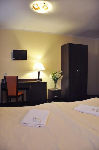 A bed or beds in a room at Hotel Pojezierze