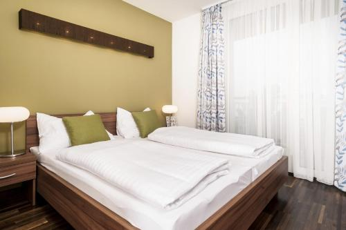 A bed or beds in a room at IG City Apartments Campus Lodge