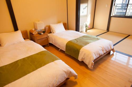 A bed or beds in a room at Wakakusa-an