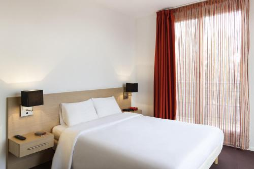 A bed or beds in a room at Aparthotel Adagio Access Saint Louis Bâle