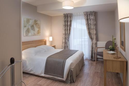 A bed or beds in a room at Domitys Les Gréements d'Or